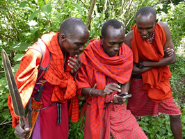 Daniel Meipuki, Patrick Koyati and David Ntiyani in the Loita Forest, learning to use the Mara EleApp by Joyce and Petter. In the enlarged photo they are very happy when first real record (sign of elephant) is saved successfully. (©ElephantVoices)